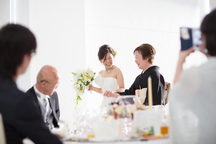 白ドレス姿と新婦と、留め袖の母が、にこやかに手をつないで中座