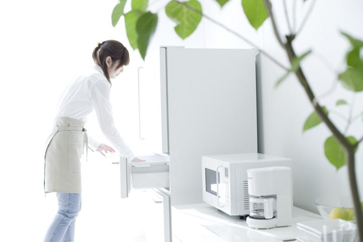真新しいキッチンで冷蔵庫を開ける女性