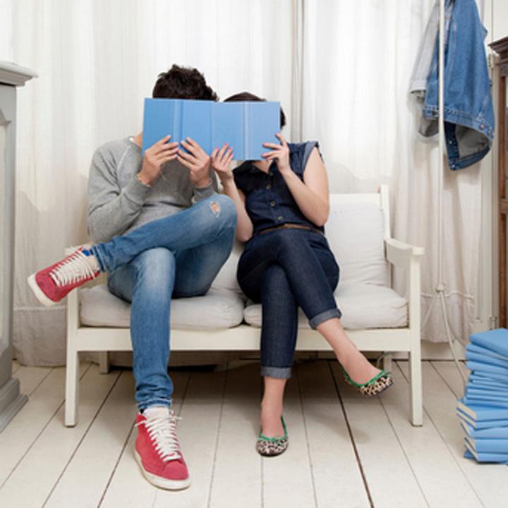 部屋の中で一緒に本を読みながら相談する夫婦