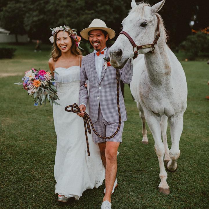 白馬を引きながら牧場を歩くふたり