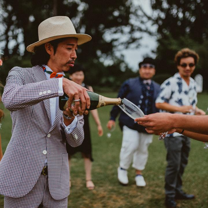 シャンパンをゲストにサーブする新郎