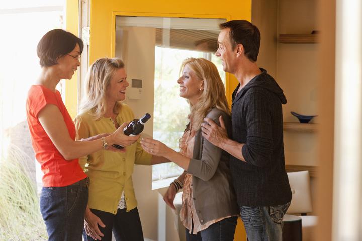 家の中で話す新婚夫婦とその義姉たち
