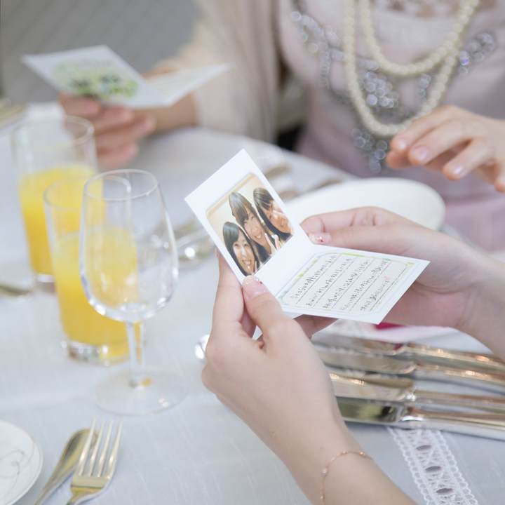思い出の写真付きメッセージカードを読むゲスト