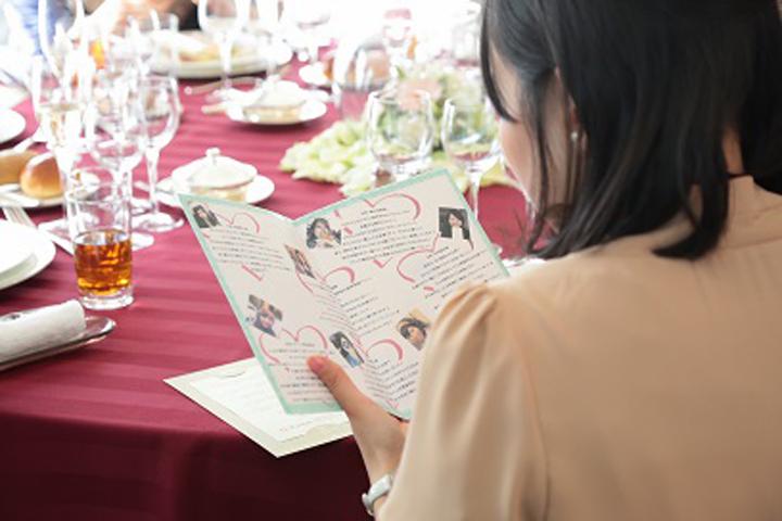 友人ゲストの紹介ブックを手に取る女性ゲスト