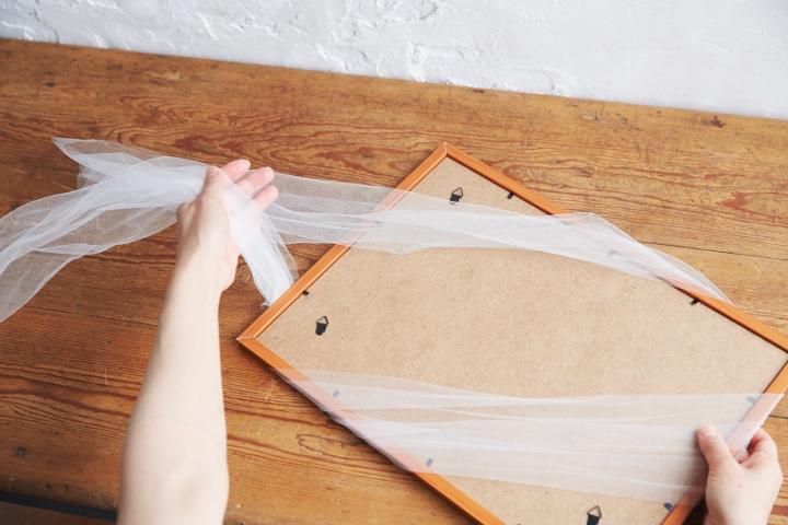 1.チュールは30cm×2m(長い)、30cm×90cm×2本(短い)に切る。長いチュールを斜めに平行になるようにウエルカムボードに巻いたら、裏面で結んで留める。