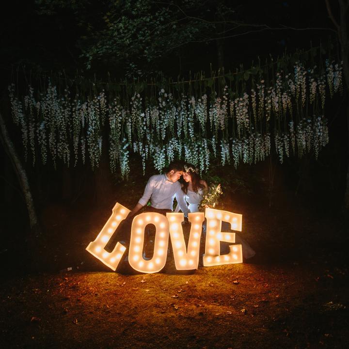 式後、LOVEのライトの前で写真撮影をするふたり