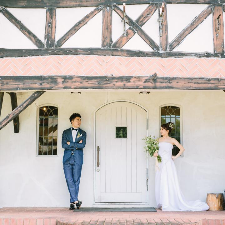 白壁の建物の前でロケフォトをするカップル