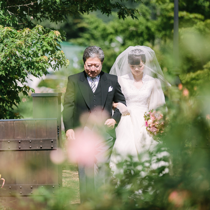 父と腕を組んで入場する花嫁
