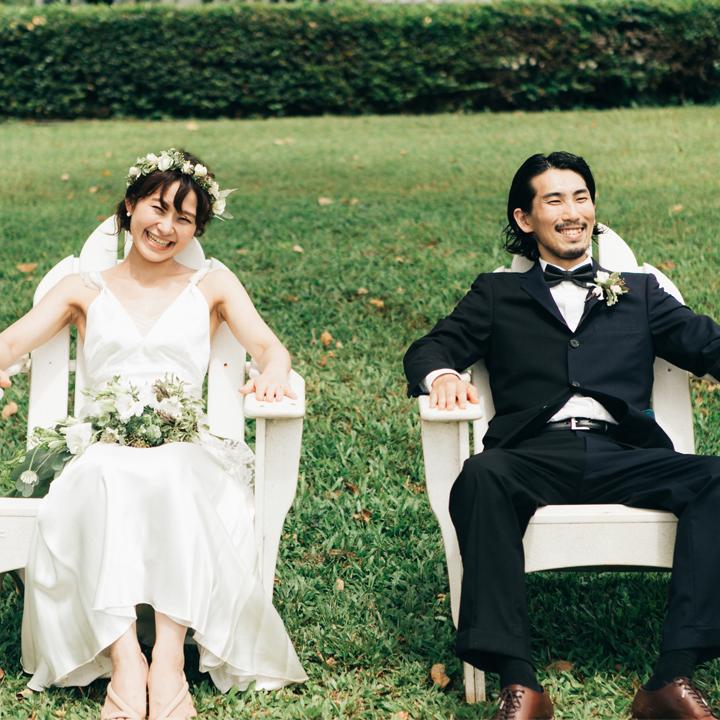 草原に置かれた椅子に座る新郎新婦