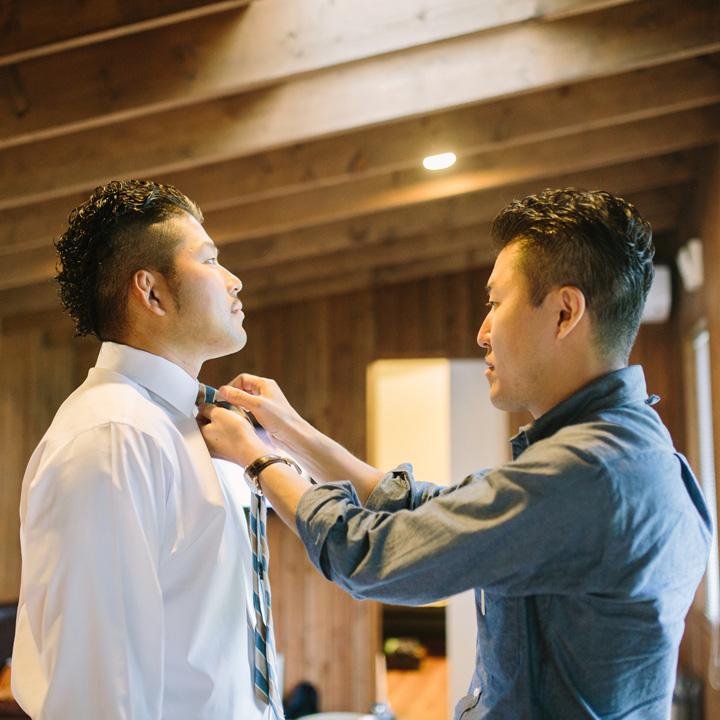 お兄さんにネクタイを結んでもらう新郎