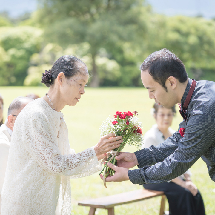 ブーケセレモニーで家族から花を受け取る新郎