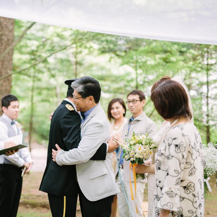 花嫁の父とハグする新郎