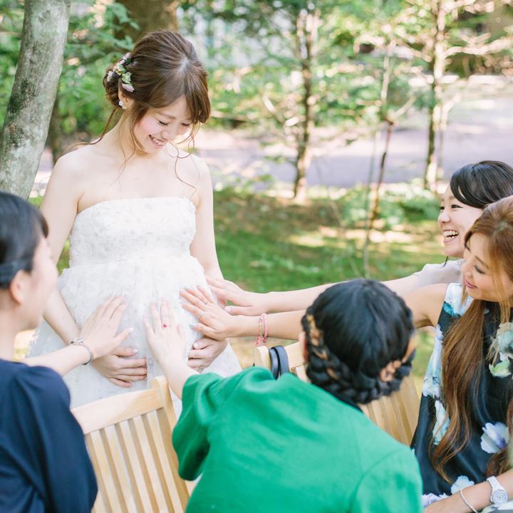 ゲストにおなかをなでてもらう花嫁