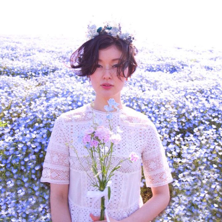 お花畑での前撮りに、ナチュラルなヘアスタイルに、ワイルドフラワーのナチュラルな花冠がマッチ。