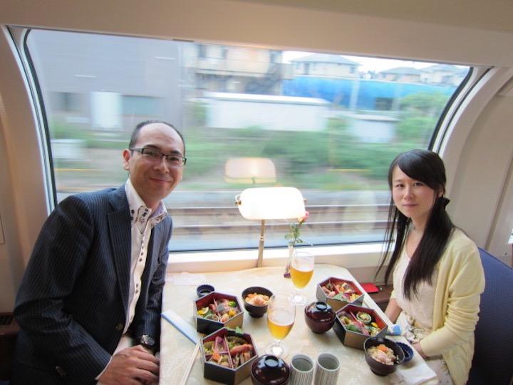 旅行とお酒が趣味というふたりが、鉄道旅行中のショット。食堂車で華やかな会席弁当を開いている