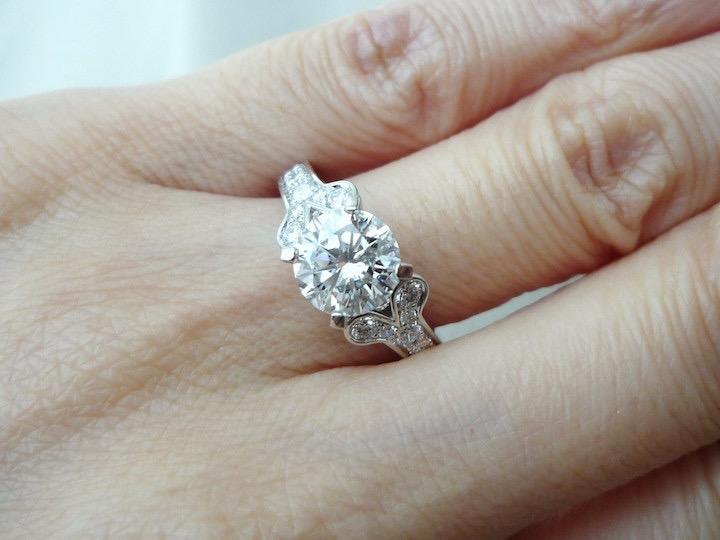 カルティエ・バレリーナ エンゲージメントリング。センターダイヤを丸みのあるアームが包み込むデザインで、ダイヤの横にメレ(小粒石)を敷き詰めたパヴェタイプ