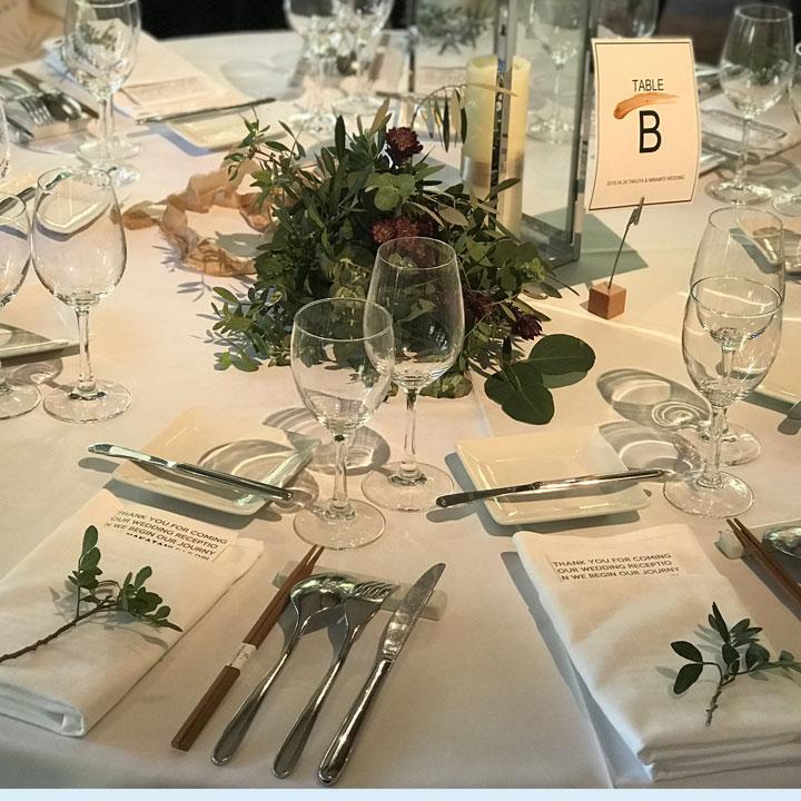 白いテーブルクロスに、中央にグリーンを主役に飾ったシンプルなテーブルコーディネートです。