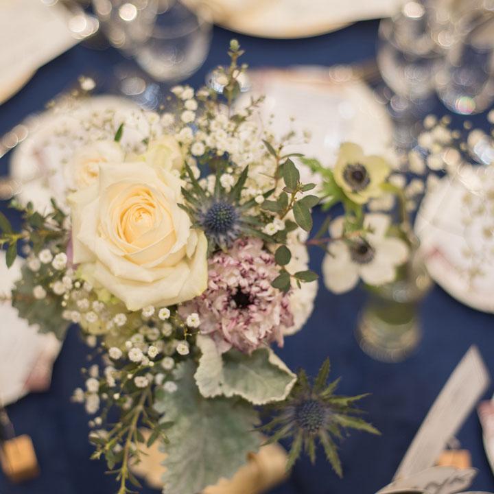 ネイビーのテーブルクロスが敷かれたテーブルの中央に、かすみ草を主としたフラワーアレンジが飾られています。