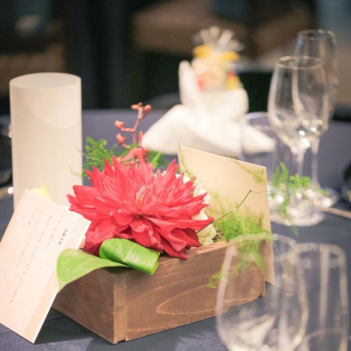 ゲストテーブルには木箱に赤い花を入れて飾ってあります。