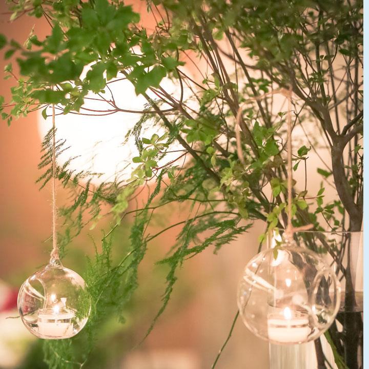 木にマルイガラスに入ったキャンドルが吊り下げられています。
