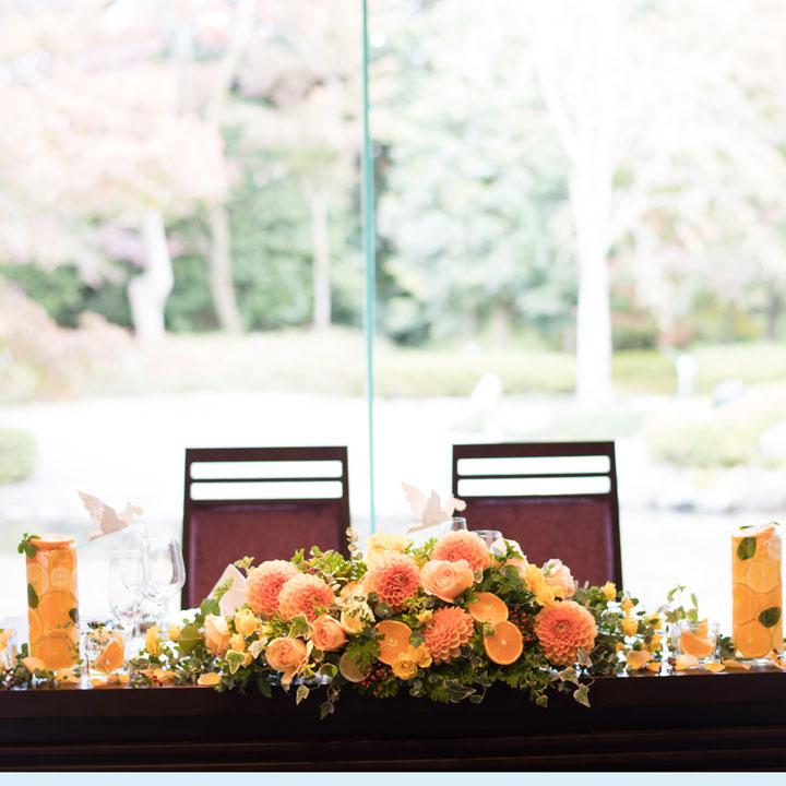 メインテーブルにもグラスに入ったレモンと同系色のお花が飾られています。