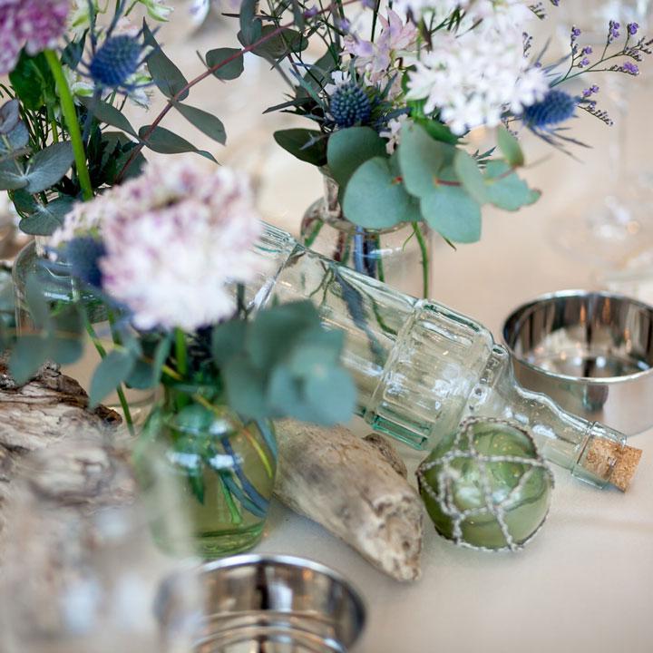 ダスティピンクを中心としたお花をガラス瓶とともにアレンジしています
