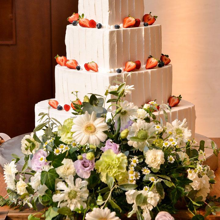 ウエディングケーキの前に、小花とグリーンを組み合わせたナチュラルなフラワーアレンジを飾っています。