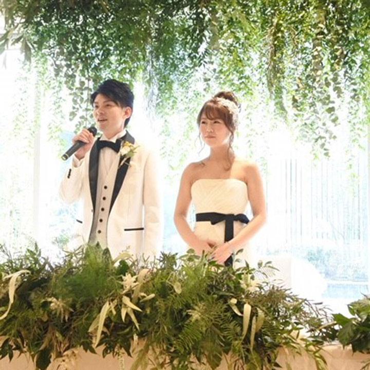 新郎新婦の後ろにカーテンのようにグリーンの葉っぱが飾られています。