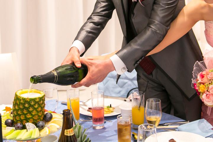 テーブルの装花だったパイナップルにシャンパンを注ぐ新郎新婦