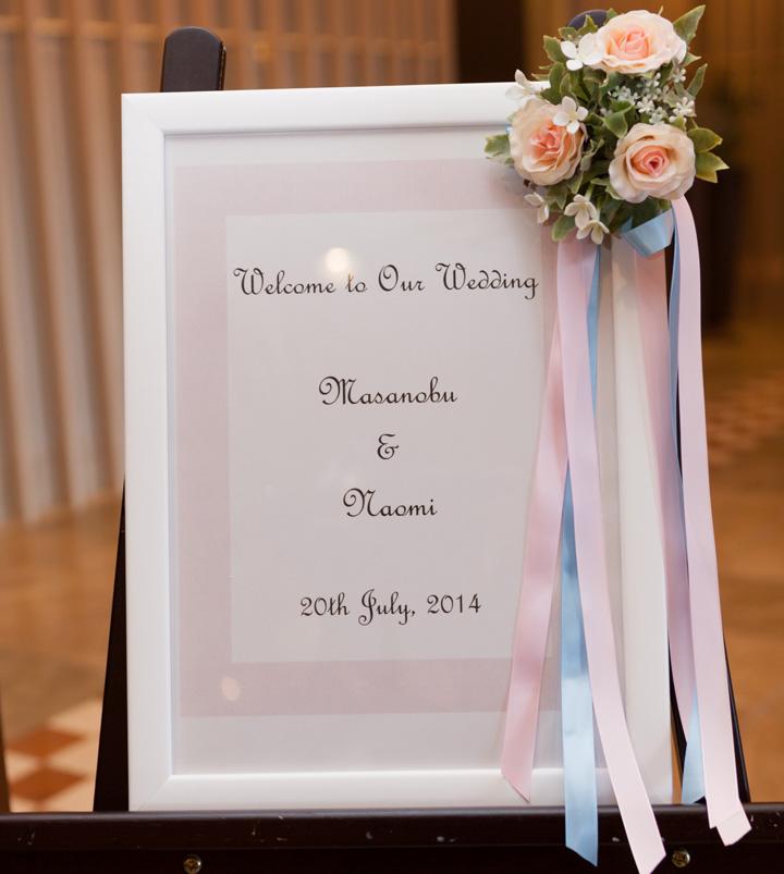 ピンクの花とリボンを飾った白い額縁のウエルカムボード