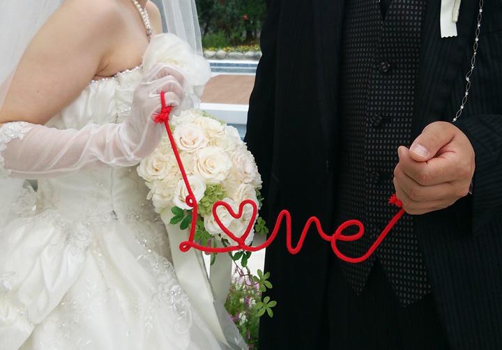 赤い毛糸を針金に巻きつけて作ったLOVEの文字を持つ新郎新婦