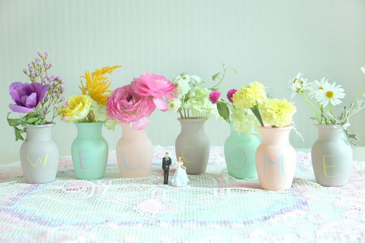 4色の小瓶を7本並べてお花を挿したウエルカムコーナー