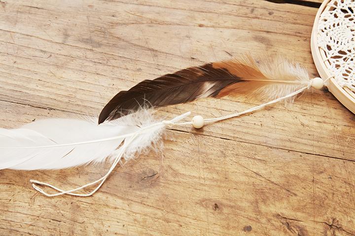 枠の真下にウッドビーズと羽を付けていく