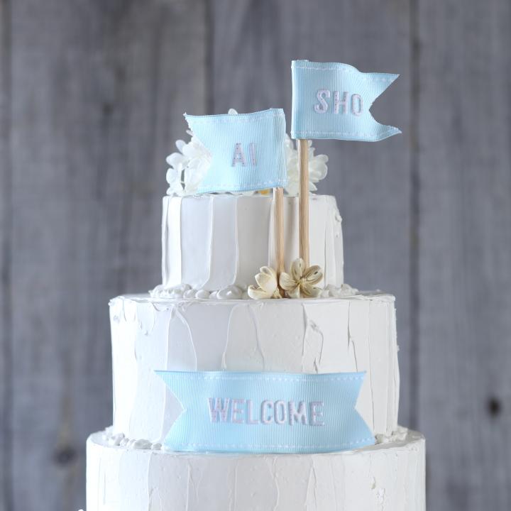 水色のメッセージフラッグを飾った白いディスプレーケーキ