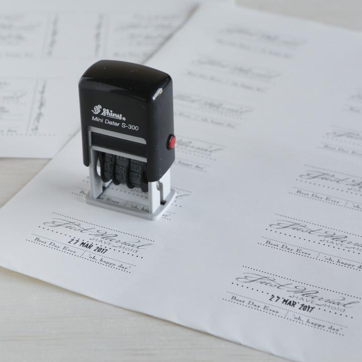 印刷したラベルシートに日付スタンプを押している様子