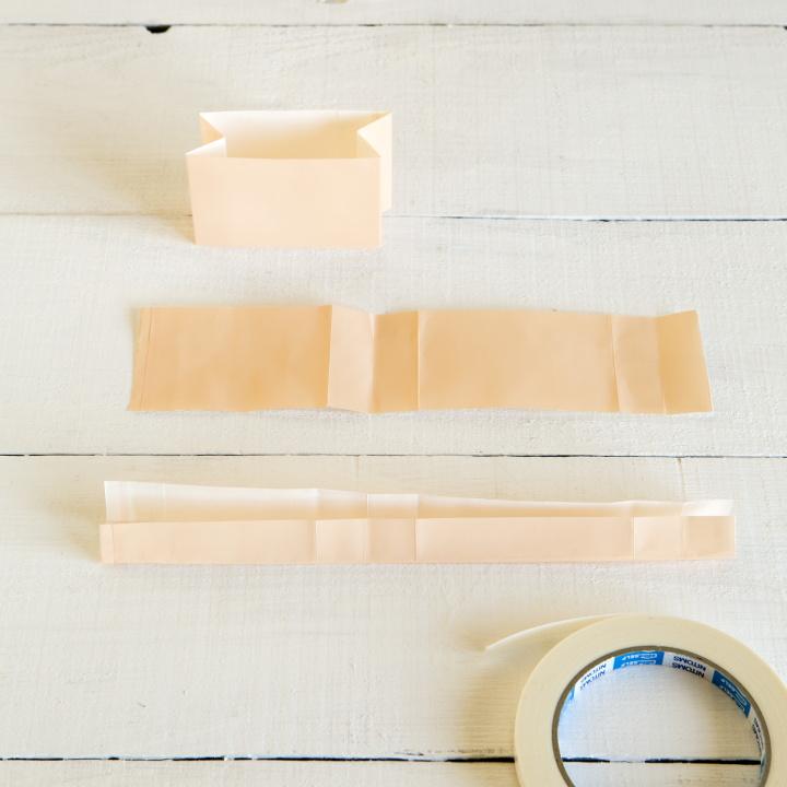切り落とした袋を広げ、三つ折りにし、両面テープで止めている様子