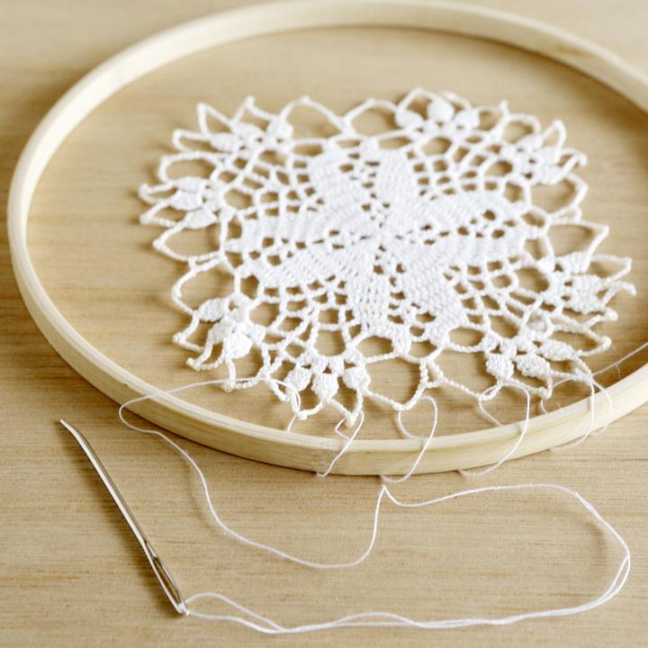 糸を使い刺しゅう枠の中央にコースターを留めている様子
