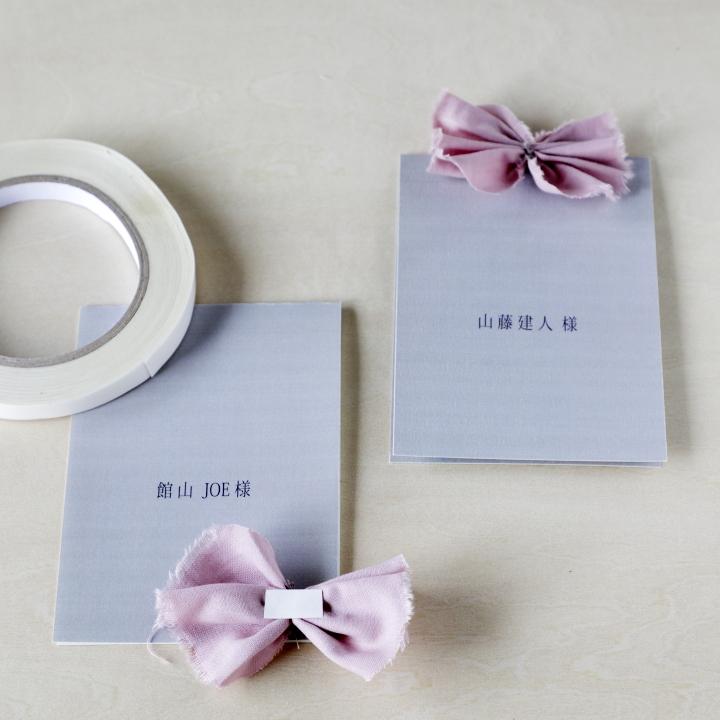 両面テープで席札にお花を留めている様子