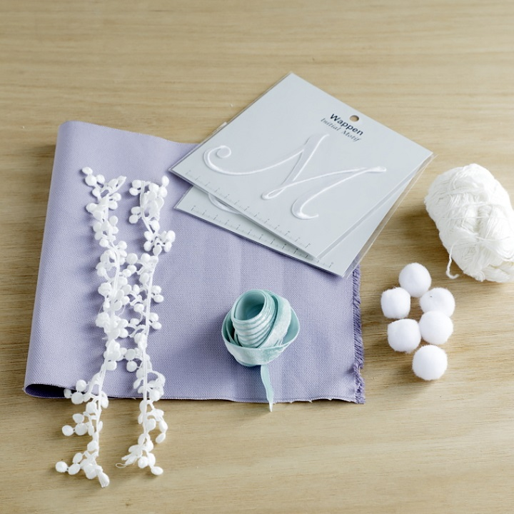 イニシャルワッペン、帆布、10mm幅のリボン、細い白色の毛糸、白色のポンポン、好みのレースリボン