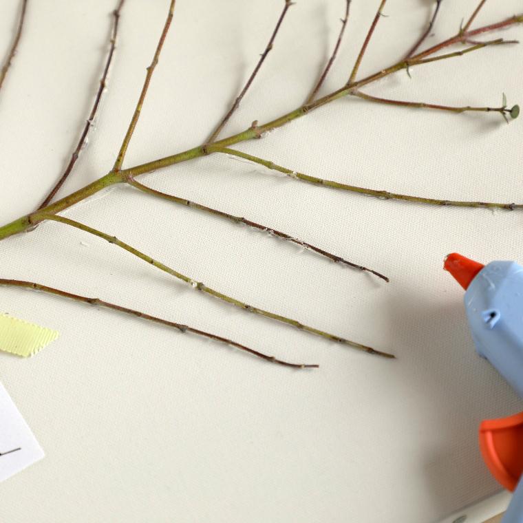 キャンバスに枝を貼っている様子