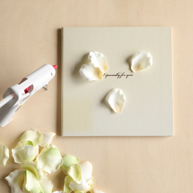台紙の表に花びらを貼っている様子