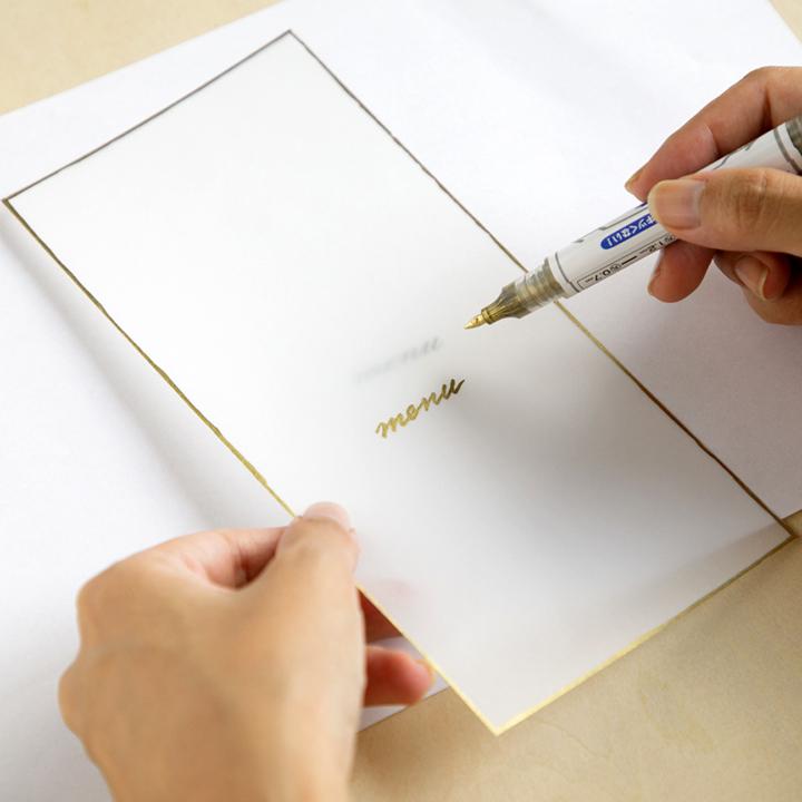 金色ペンで文字をなぞっている様子