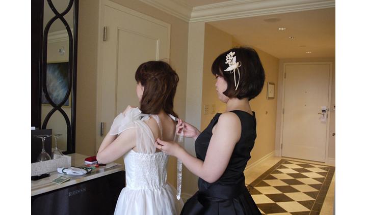 先輩カップル 挙式・披露宴スナップ 花嫁の支度中 妹がチョーカーを結ぶ