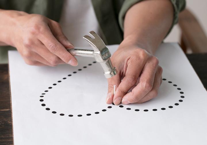 2、板に型紙を置き、金づちで釘をまっすぐに打つ