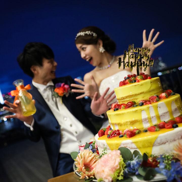 夜景をバックに新郎新婦がウエディングケーキの前に立っています。