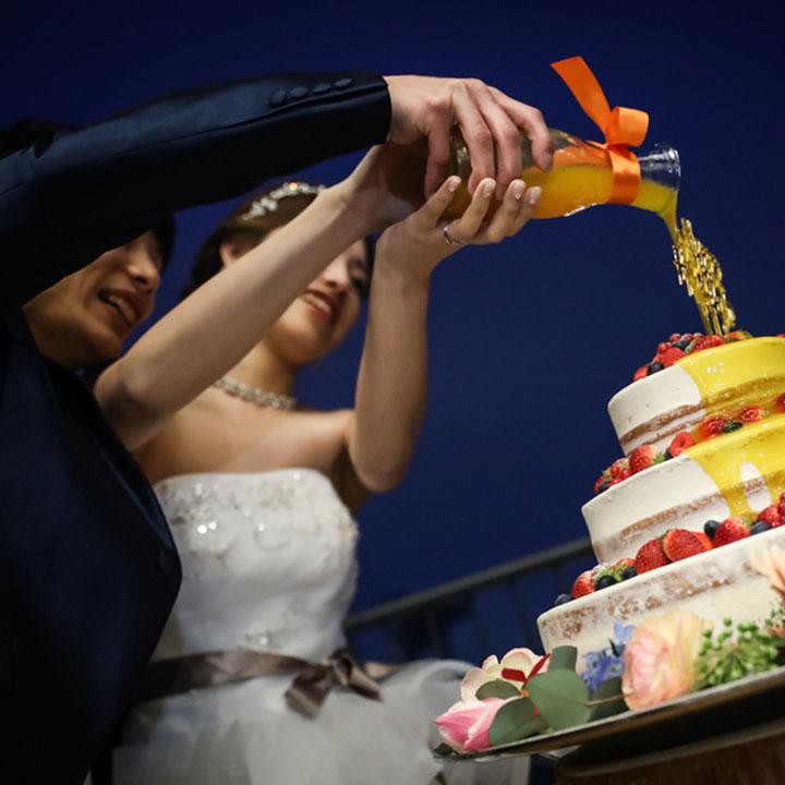 ウエディングケーキに新郎新婦が黄色のソースをドリップします。