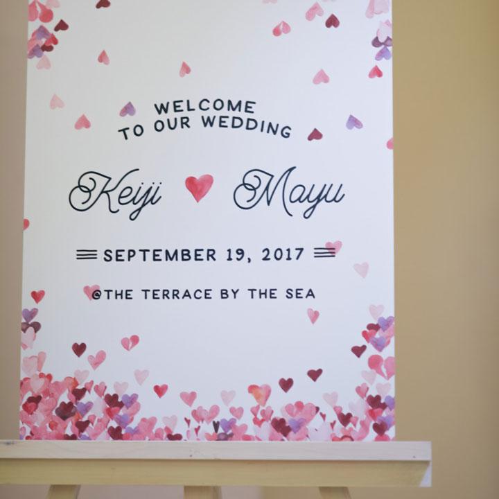 ハートがちりばめられ、新郎新婦の名前が中央に描かれたウェルカムボードです