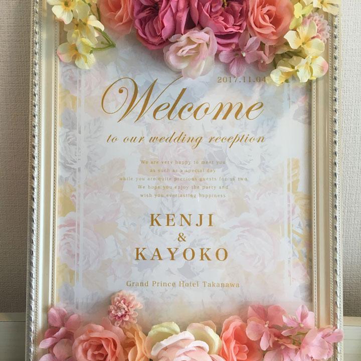 繊細な英字が描かれ、造花で飾られたウェルカムボードです