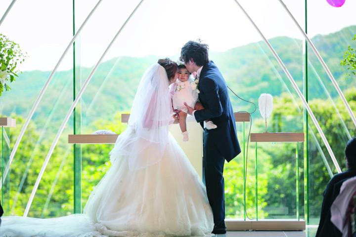 子どものほっぺに誓いのキスをしているパパとママ