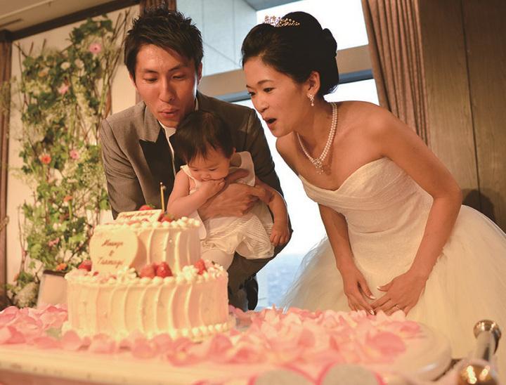 親子3人でケーキのろうそくの火を吹き消しているシーン